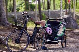 Kind mit Helm und Fahrradanhänger