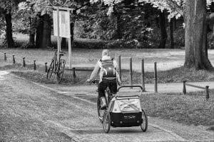 Mutter fährt mit Baby Fahrradanhänger